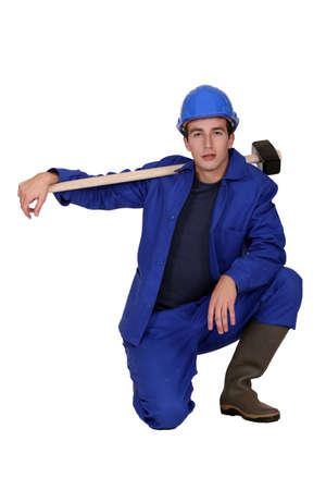 sledgehammer: Man with sledge-hammer kneeling Stock Photo