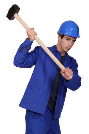 journeyman technician: construction worker using a sledge hammer