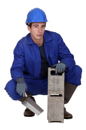 Worker holding a cinder block and trowel photo