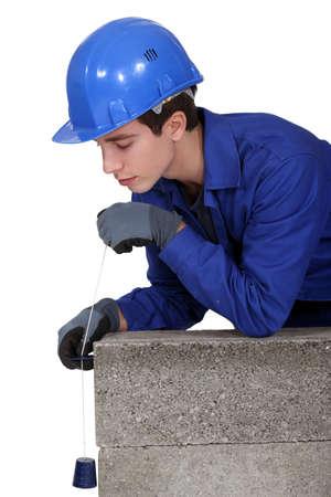 plumb: Tradesman holding a plumb line