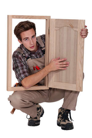 jumpsuite: a young carpenter showing a piece of furniture