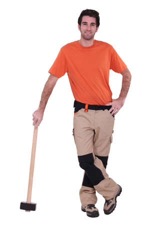 odd jobs: Handyman wearing patched trousers and leaning against a mallet