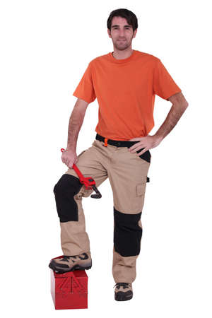 modifiable: Manual worker with foot on tool-box Stock Photo