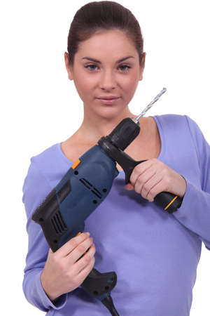 young female apprentice holding electric drill photo