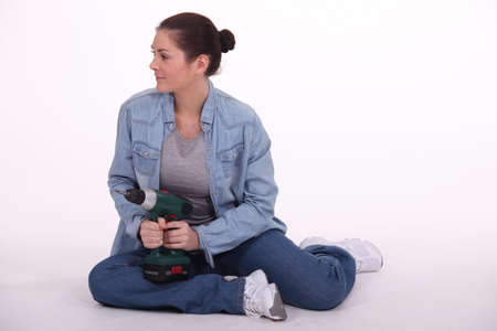 drill floor: Woman sat on floor with power drill Stock Photo