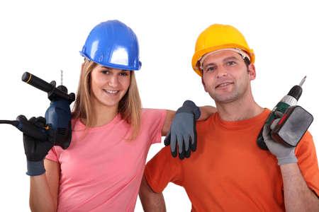 craftsman and craftswoman holding drills photo