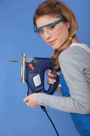 woodworking: Attractive woman with band-saw