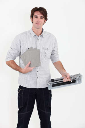 tile cutter: Man using a manual tile cutter Stock Photo