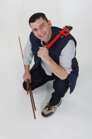 kneeled: A plumber with copper pipes and a wrench. Stock Photo