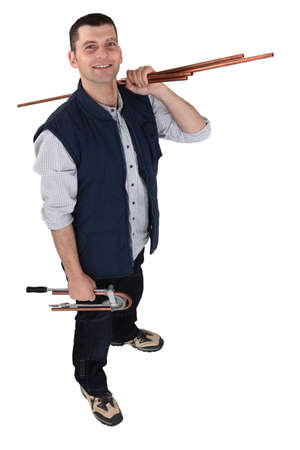 high angle shot: plumber posing with copper pipes over his shoulder