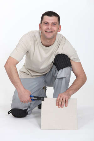kneeled: A kneeled tiler. Stock Photo