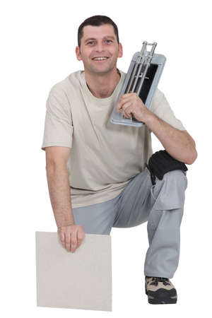 tile cutter: Man kneeling with tile cutter Stock Photo