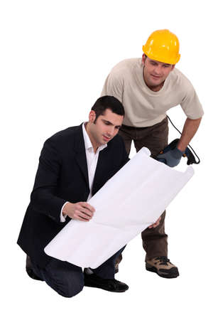 Construction worker consulting with an engineer over a drawing photo