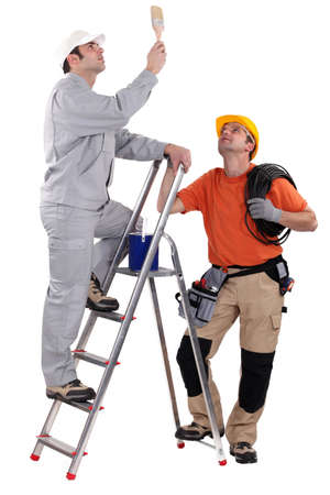 A painter and an electrician looking at the ceiling. photo