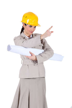 businesswoman holding a blueprint and pointing at something photo