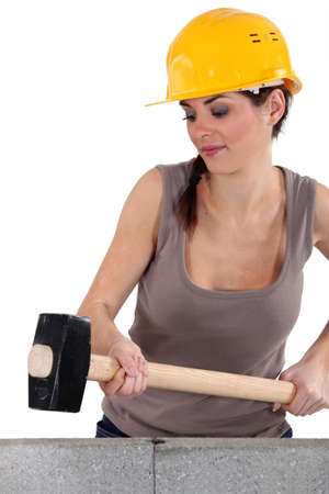 destroying: Woman hitting wall with sledge-hammer Stock Photo
