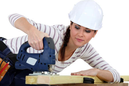 handtool: Female carpenter using a jigsaw. Stock Photo