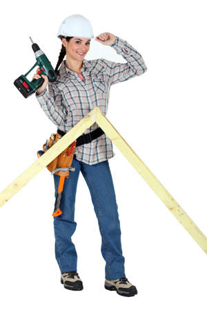 portrait of lovely female carpenter holding electric drill photo