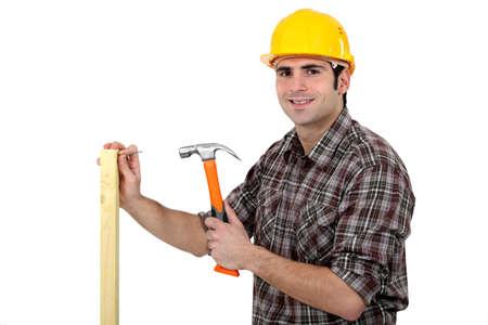 Carpenter driving a nail in a beam, studio shot photo