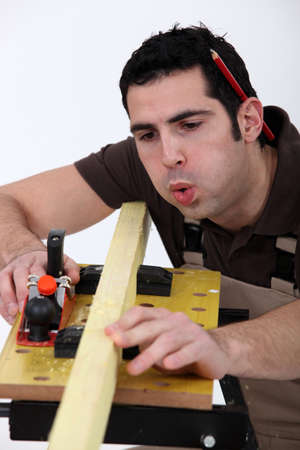 puckered: Tradesman blowing shavings off of a wooden plank