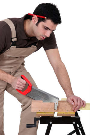 Man cutting a piece of wood photo