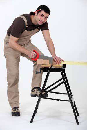 Male carpenter sawing. photo