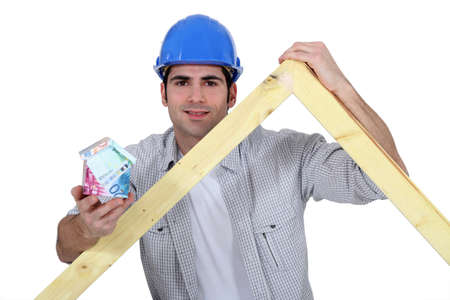Carpenter stood with wooden truss and money Stock Photo - 13883692