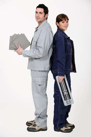 Man and woman holding tiles and cutter photo
