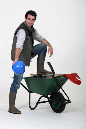 Construction worker showing off his hard hat, wheelbarrow and tools photo