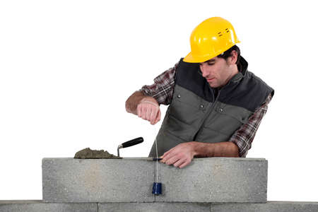 Tradesman using a plumb-bob photo