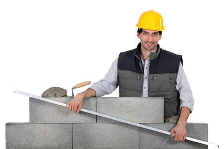 Bricklayer with a steel rule photo