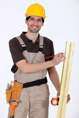 tools belt: Handyman measuring a wooden plank