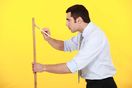 paintjob: Businessman painting plank of wood