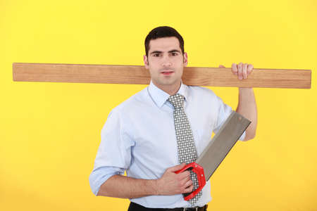 Businessman stood with saw and plank photo