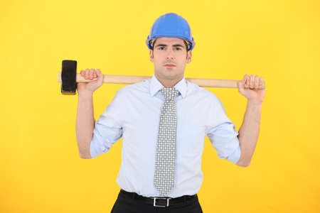 Architect holding sledge-hammer across shoulders photo