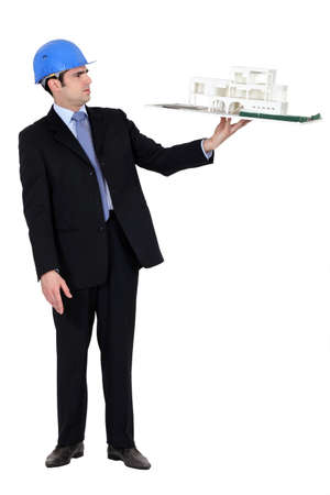 thirty something: architect in suit holding model looking annoyed