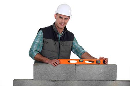 stonemasonry: Construction worker using a bubble level