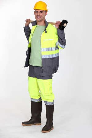 Man holding sledge hammer over shoulder photo