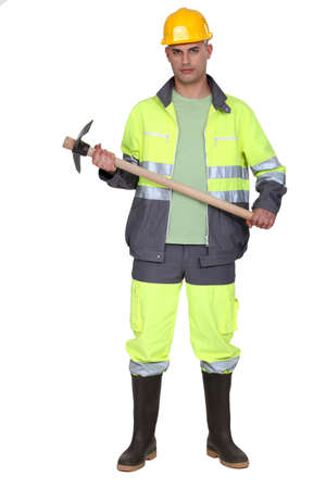 safety boots: A man holding a pickaxe.