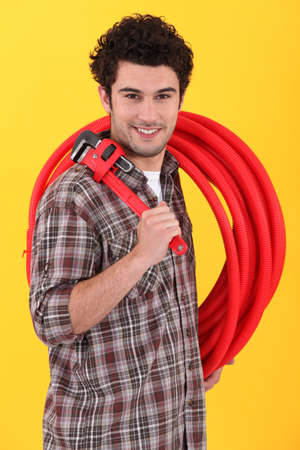 Plumber holding wrench and length of plastic pipe photo