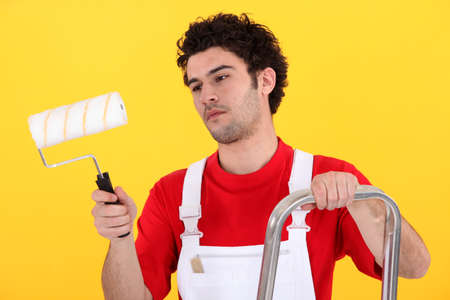 Man on step-ladder holding paint roller photo