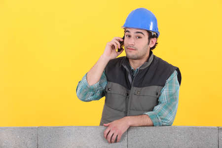 young bricklayer on the phone behind concrete wall against yellow background photo