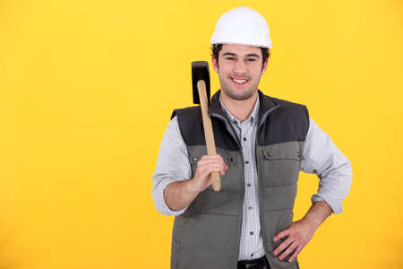 Smiling laborer on yellow background photo