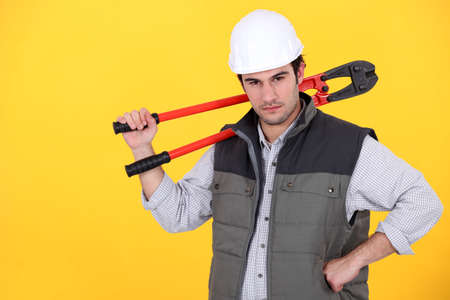 Tradesman carrying a pair of large clippers on his shoulder photo