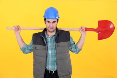 Scowling labourer carrying a shovel Stock Photo