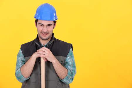 Man leaning on sledge-hammer handle Banco de Imagens