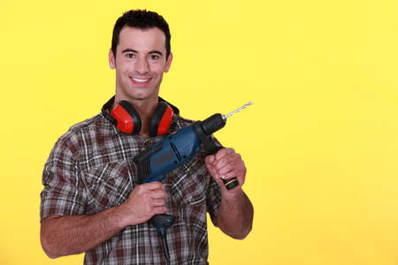 Man with power drill and earmuffs photo