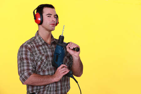 Man with earmuffs and drill photo