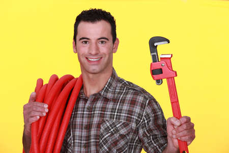unworried: Man holding a pipe wrench and carrying corrugated tubing around his shoulder