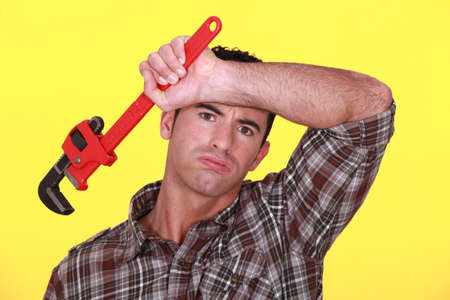 perspire: exhausted craftsman with adjustable spanner against yellow background Stock Photo